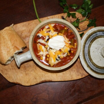 Veggie Chili in a crock with french bread and fresh parsley near by.