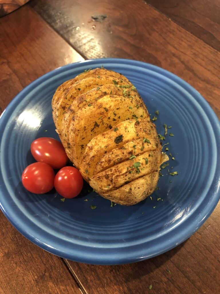 Easy Hasselback Potato with garlic butter on a blue plate with cherry tomatoes