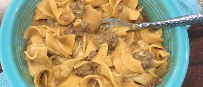 Sour Cream mixed into the Beef Stroganoff in a blue bowl with a fork.