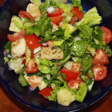 Panzanella salad in a blue bowl.