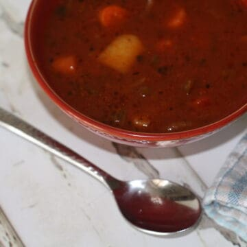 Veggie soup in a red bowl with a spoon near by.