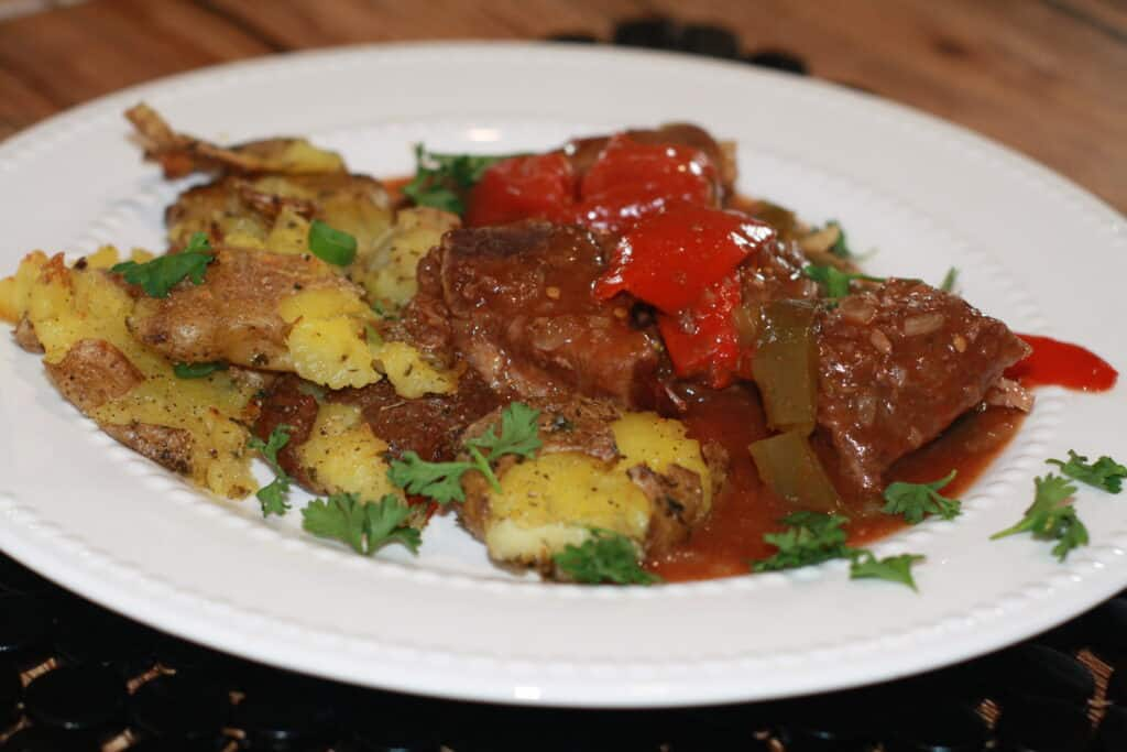 Potatoes with swiss steak on a plate