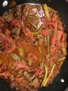 Sauteing beef, celery, tomatoes and soy sauce in a pan