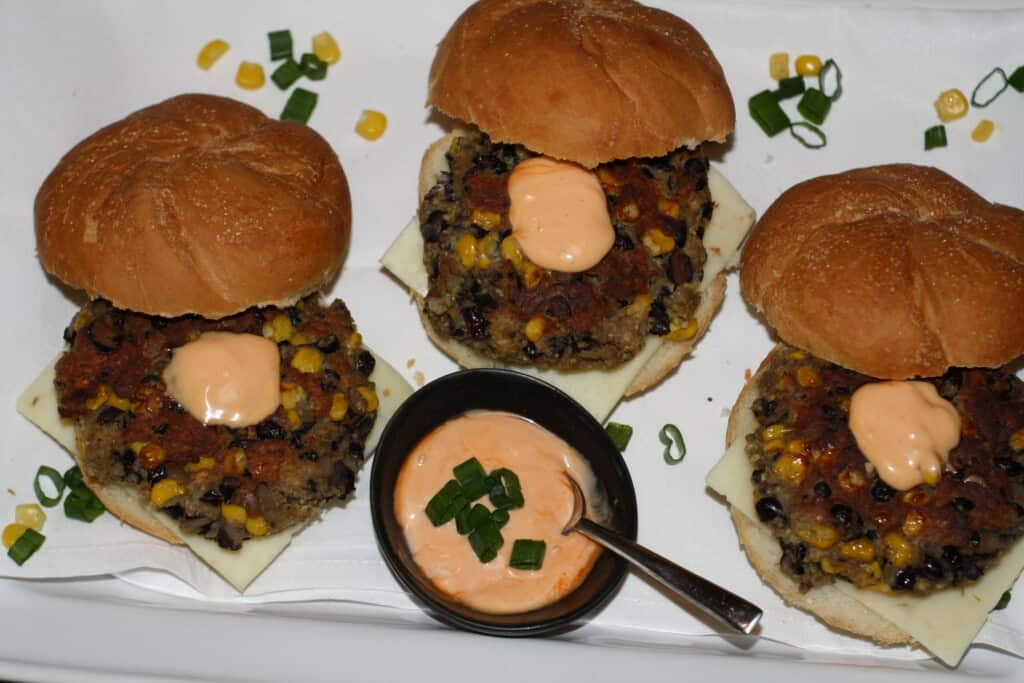 3 blackbean veggie burgers in rolls with cheese and chipotle mayo.
