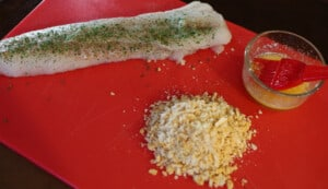 Cod, rits cracker crumbs and melted butter on a red cutting board