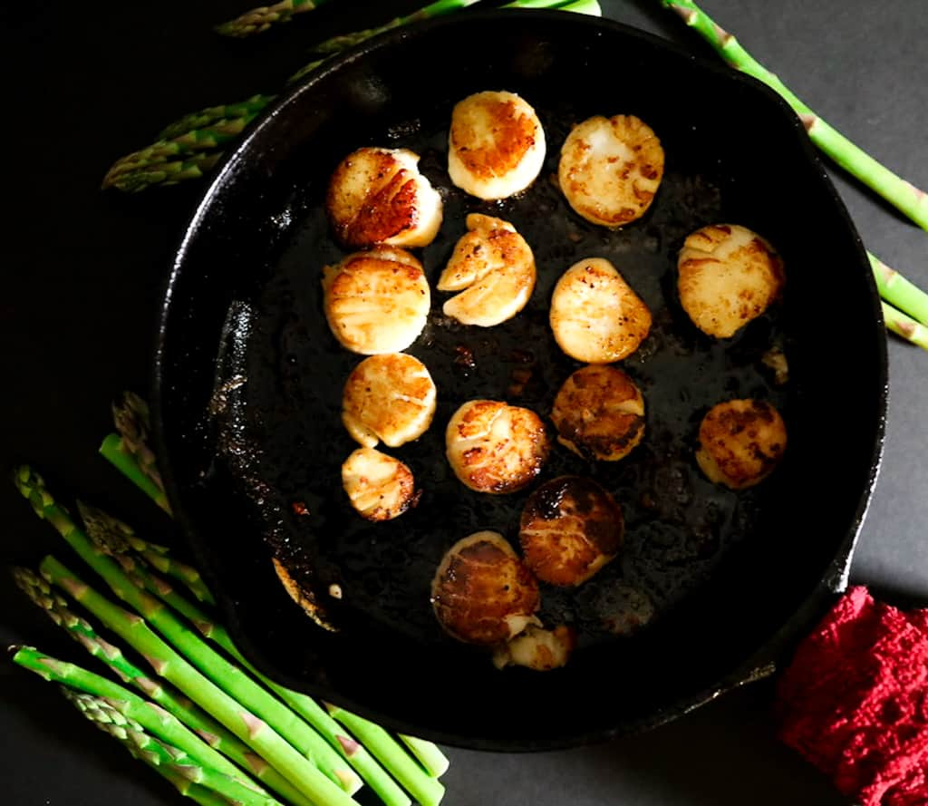 Pan-Fried Scallops in a cast-iron pan with asparagus off to the side