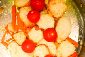 Skillet potatoes with carrots and tomatoes in a pan