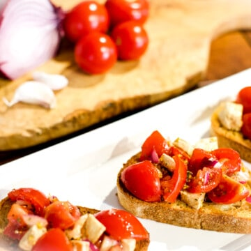 The best caprese bruschetta on a plate with an onion, tomatoes, and garlic off to the side.
