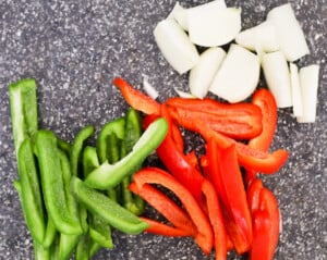 Green and red peppers sliced into strips and an onion cut into eighths