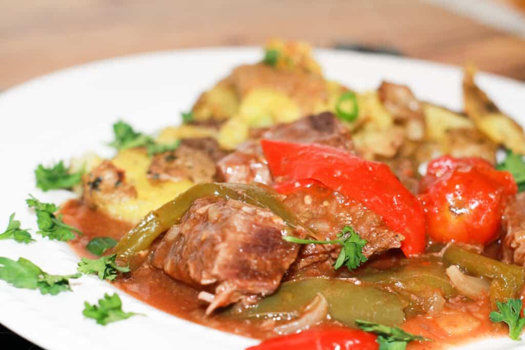 Savory Swiss Steak Creole with parsley garnish