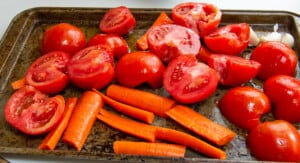 Tomatos and carrots cut for roasting in the oven on a backing sheet.