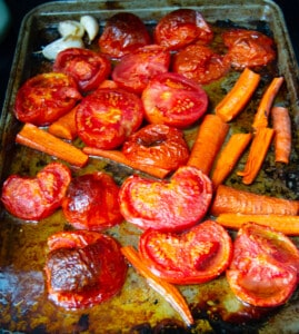 Roasted tomatoes, carrots and garlic on a baking sheet.