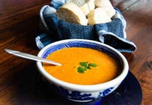 Roasted tomato feta soup in a blue and white bowl with french bread off to the side.